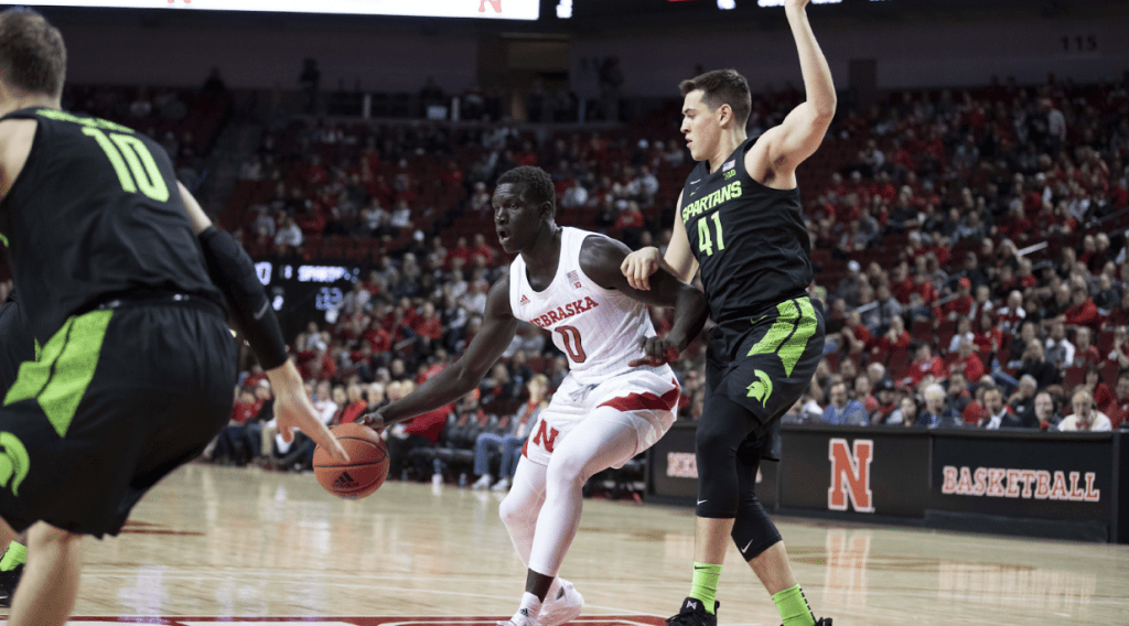 Akol Arop (in white) plays in a basketball game against Michigan State University Photo: Nebraska Athletic Communications Office